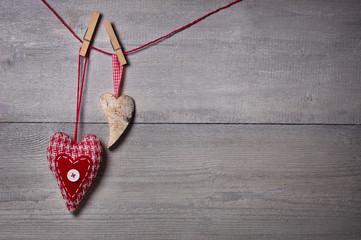 Zwei Herzen an roter Leine vor Holzwand