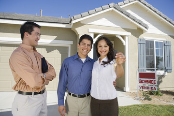 Young couple buying house holding keys