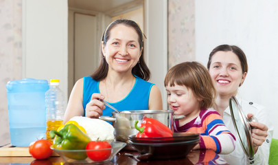 Happy women  with child  cooking veggie lunch
