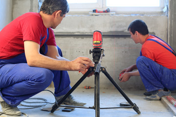 workers makes measurements with laser level tool