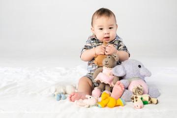 Baby boy playing with stuffed toys in studio