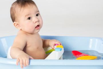 Baby boy bathes in a bathtube with toys