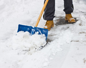 Clearing snow with shovel after storm