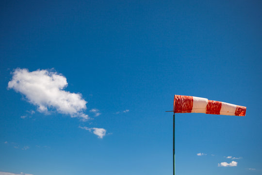red wind vane against a blue sky
