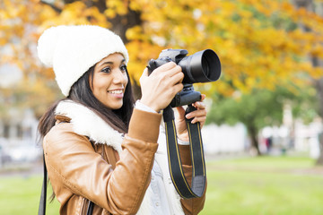 Smiling girl taking pictures outdoor.