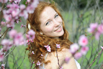beautiful red-haired girl among the flowering trees
