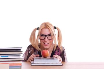 fröhlich lächelndes Mädchen mit Büchern und einem Apfel