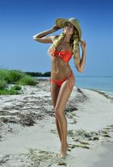 Bikini model in straw hat posing sexy at tropical beach location