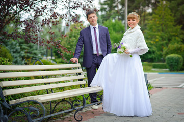 bride and groom in the park, a wedding bouquet, wedding dresses