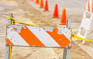 Old wood,metal construction barricade on broken pavement