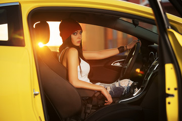 Fashionable young woman sitting in a car