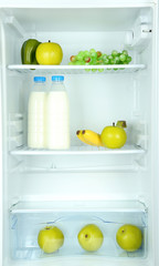 Milk bottles, vegetables and fruits in open refrigerator.