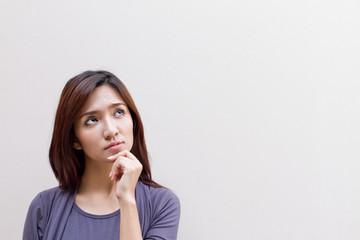 thinking woman, facing upward on plain background