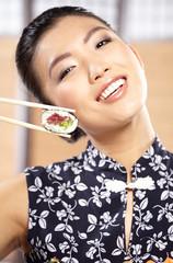 Beautiful young woman eating sushi. Shallow depth of field, focu