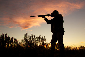 Hunter Silhouetted Shooting at Sunset Wall mural