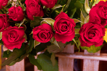 many red roses in brown basket