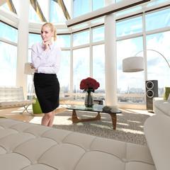 junge blonde Geschäftsfrau in luxuriösem Appartment