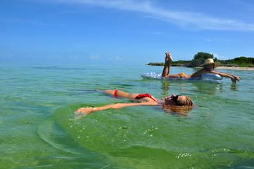 Sexy girl resting at mattress at tropical water