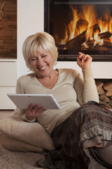 Adult female using digital tablet computer by fireplace