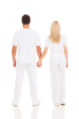 back view of young couple holding hands