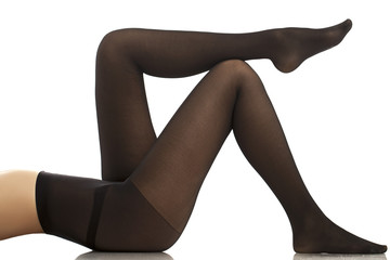 Beautiful girl in black pantyhose. White background.