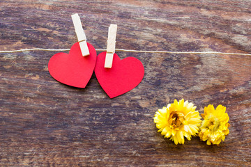 Valentine's day card with two red hearts symbol on a wooden  sur
