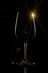 Wine glass on black background with sun flare