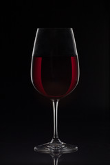 Red wine glass with wine on black background