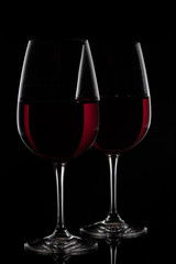 Two red wine glasses with wine on black background