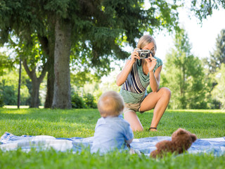 Mother Photographing Baby Boy At Park