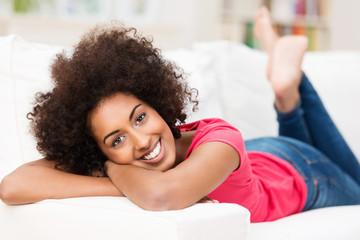 junge frau liegt entspannt auf der couch