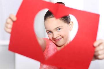 Obraz Piękna dziewczynka patrzy przez kartkę z wyciętym serduszkiem - fototapety do salonu