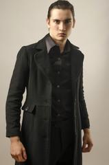 Beautiful man wearing a black shirt, pants and a long coat