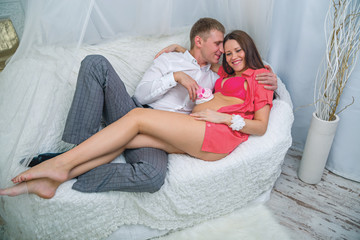 young man embracing pregnant woman on the couch