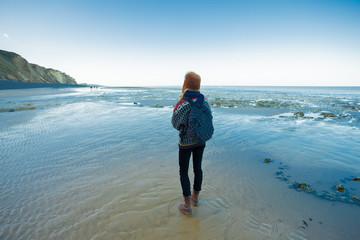 woman is trekking on the beach
