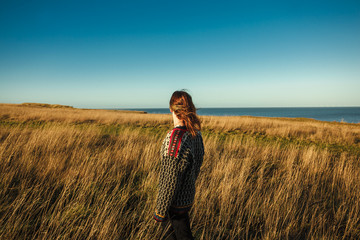 Young woman standing in meadow by the sea