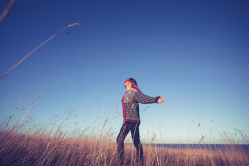 Young woman expressing freedom in field at sunset