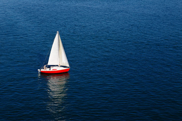 A lone white sail of a red sailboat on a calm blue sea