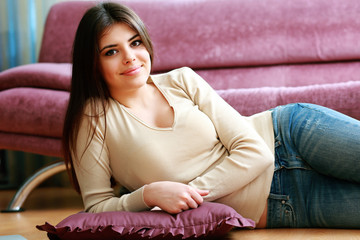 Young happy smiling woman lying on the floor at home