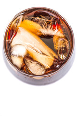 Cola drink with ice cubes in a short glass over white background