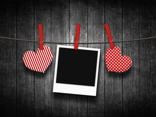 hearts hanging on clothesline over wooden background