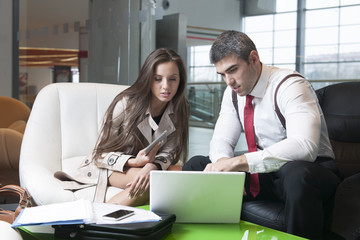 Businessman and businesswoman at meeting with laptop
