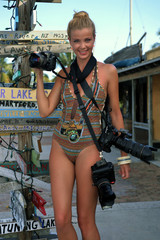 Model holding photo cameras at tropical location