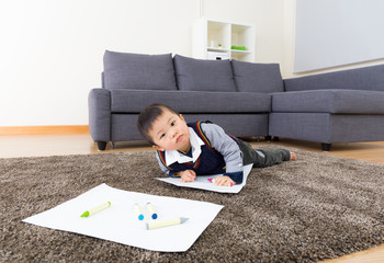 Asian baby boy drawing picture at home