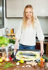 woman cooking  fish with potato in sheet pan