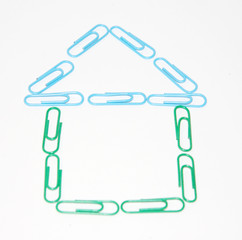 House from many green and blue plastic paper clips on white.