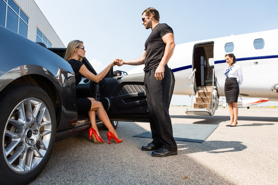 Bodyguard Helping Elegant Woman Stepping Out Of Car