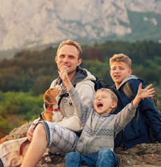 Father with sons and favorite puppy on the mountain walk