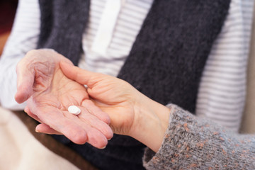 Hands of senior patient and caregiver with medication