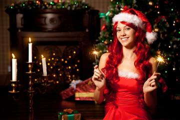 Young beautiful smiling santa woman near the Christmas tree. Gir